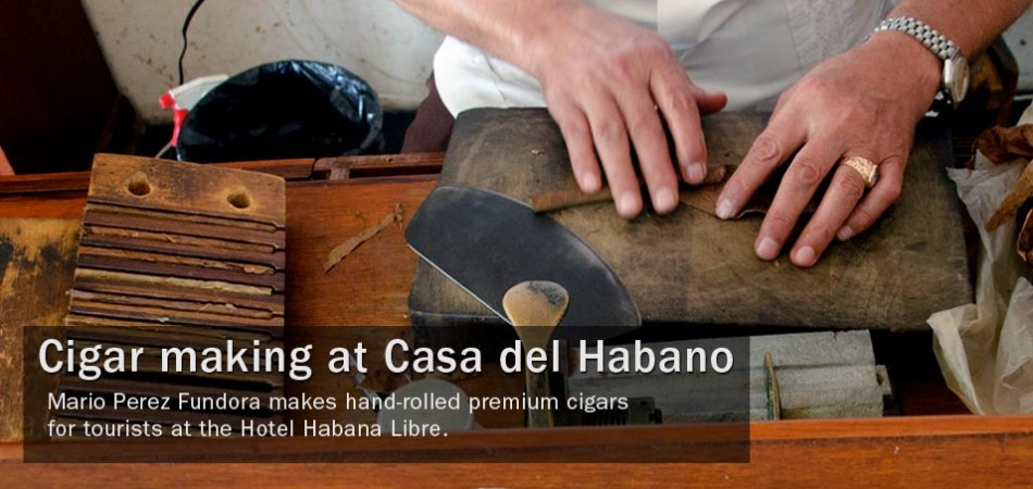 Mario Perez Fundora makes hand-rolled premium cigars for tourists at the Hotel Habana Libre.