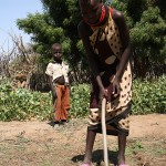 Rose, a married girl who works in the garden of the village of Vangagetei, uses a tool fashioned from a tree branch to prepare a plot for seed sowing.  (Lindsey Welling)