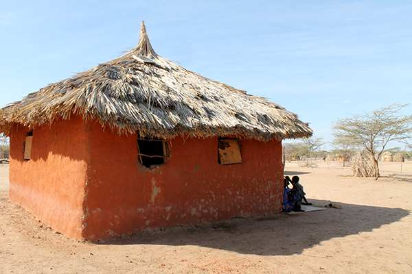 Simon Ekaale and his wife lounge in the shade of their mud hut in Turkwel, Kenya, January 17, 2013.  Near the horizon are the traditional palm-frond homes found throughout the region. (Nicole Bansen)