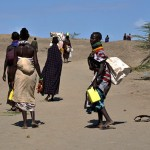 Turkana women return home from gathering water at the semi-dry river bed in the village of Kerio, where 3,000 Turkana live. Some women made a living selling the water they collected from the river bed for five Kenyan shillings per liter. (Deanna Del Ciello)