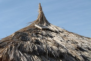 The solar panel sits atop the thatched roof of Simon Ekaale's mud hut, January 17, 2013.  The panel provides power for an electric hair trimmer, lamp and a radio, and provides a battery-charging source. (Nicole Bansen)
