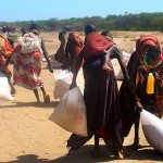 Women walk up to nine miles from their villages and homesteads to collect sacks of food aid from a central point in the village of Kerio. Most food aid consisted primarily of grain, leaving nutrional gaps in the diets of those who relied on it. (Jessica Stallone)
