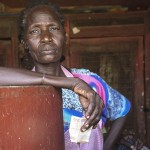 "Arot, co-owner of Lodwar's local butchery, collects 100 shillings, approximately $1, after a transaction.  ""Instead of beng scattered, let's be brought together to have one common thing,"" she said of the 10, mostly widowed, women who co-own the 40-year-old shop. (Chelsea Katz)"