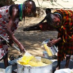 Two women mix bags of corn-soy blend and vegetable oil from a malnutrition clinic set up by Merlin, a U.K.-based aid organization, which is being rationed off to their village, Koono.  Merlin gets all of its supplies from the Kenyan Ministry of Health and the World Food Programme, Geoffrey Murrthi, a nutrition officer for Merlin, said.   (Lindsey Campbell)