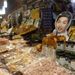 Packaged dried fish and squid sit in front of a paper cutout of Song Joong-ki, a popular South Korean actor, model and host. Photo by Taylor Ha.
