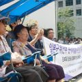 Two of the less than 50 South Korean comfort women sit silently as the crowd that engulfs them bellows for their justice.