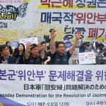 "Behind the crowd of 300, Korean characters bolded in red and blue read: ""Park Geun-hye regime, immediately abolish the comfort women agreement."""